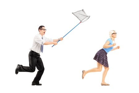 Full length portrait of a young woman trying to runaway from guy with butterfly net isolated on white background photo