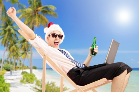 Excited man with santa hat on a beach chair holding a beer and working on a laptop, on a tropical beach photo