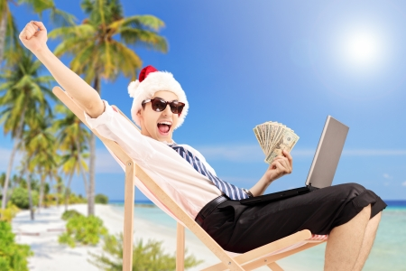 man money: Excited man with santa hat on a beach chair holding banknotes and working on a laptop, on a tropical beach