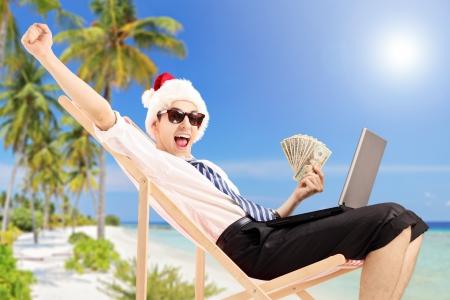 Homme excité avec chapeau de Père Noël sur une chaise de plage tenant billets et de travailler sur un ordinateur portable, sur une plage tropicale