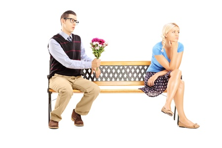 Male giving a bunch of flowers and uninterested blond female sitting on a wooden bench isolated on white background photo