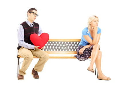 Male holding a red heart and disappointed blond female sitting on a wooden bench isolated on white background photo
