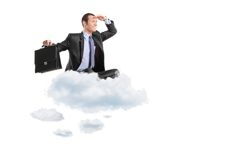 Young businessman with suitcase sitting on a cloud isolated on white background photo