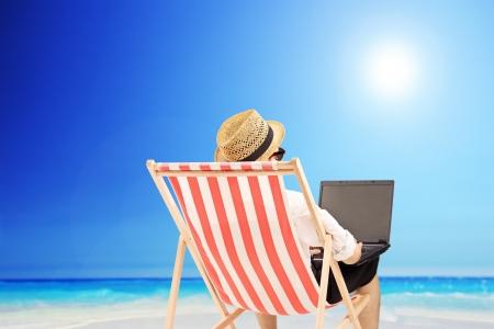 Giovane uomo su una sedia da esterno a lavorare su un computer portatile, su una spiaggia di un mare