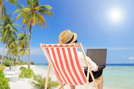 Hombre joven en una silla al aire libre de trabajo en un ordenador portátil, en una playa tropical
