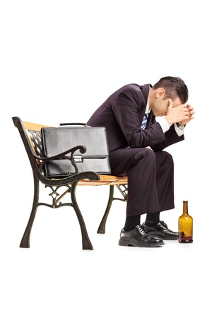 despair: Disappointed young businessperson sitting on a wooden bench isolated on white background Stock Photo