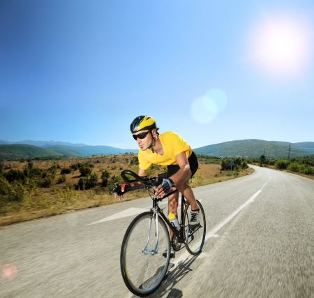 bikes: Male cyclist riding a bike on an open road on a sunny day, shot with a tilt and shift lens