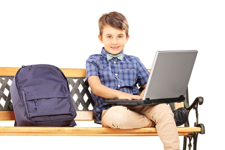 sitting on a bench: Schoolboy sitting on a wooden bench with school bag next to him and working on a laptop isolated on white background Stock Photo