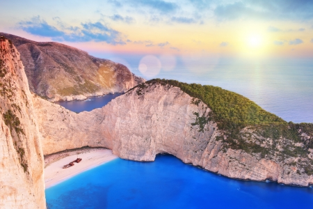 greece shoreline: View of Zakynthos island, Greece with a shipwreck on the sandy beach, at sunset