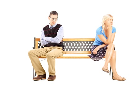 people problems: Young couple sitting on a wooden bench after having an argument isolated against white background Stock Photo