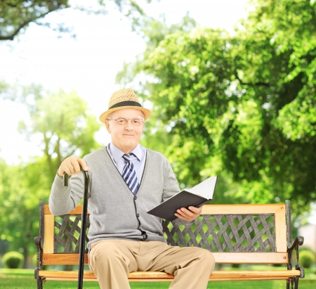 Senior man sitting on a wooden bench and reading a book, in a park, shot with a tilt and shift lens photo