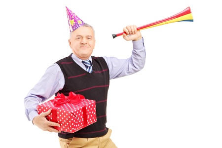 Mature man wearing a party hat and holding a gift and horn isolated on white background photo