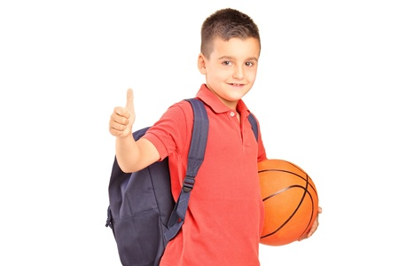 boy basketball: School boy with backpack holding a basketball and giving a thumb up isolated on white background