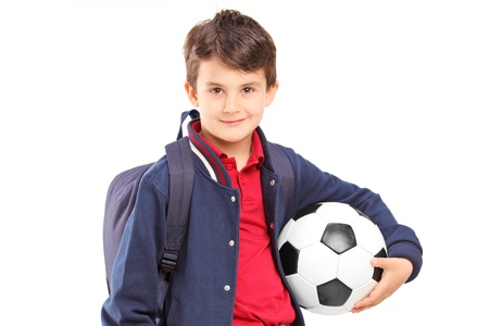 niño con mochila: Colegial que sostiene un balón de fútbol, ??aislados en fondo blanco
