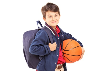 basket ball: Schoolboy with backpack holding a basketball, isolated on white background