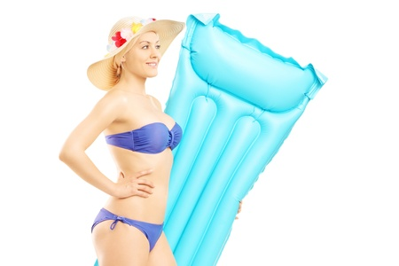Young woman in swimsuit holding a swimming mattress isolated on white background photo