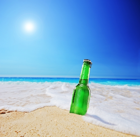 tilt shift: Beer bottle on a sandy beach with clear sky and wave, shot with a tilt and shift lens Stock Photo