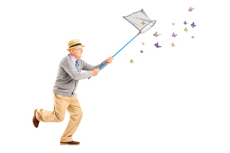 Full length portrait of a mature man running and catching butterflies with net isolated on white background photo