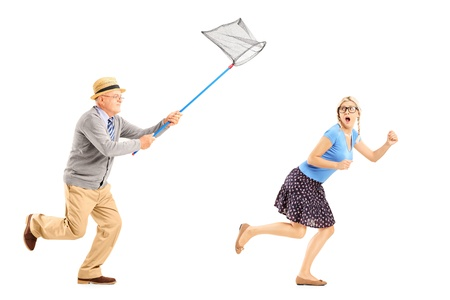 Full length portrait of a scared young female trying to runaway from mature man with butterfly net isolated on white background photo