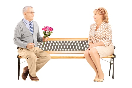 chivalry: Mature gentleman giving a flower bouquet to a woman and sitting on a bench isolated on white background