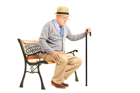 sitting in the bench: Senior man with a cane sitting on a bench isolated on white background Stock Photo