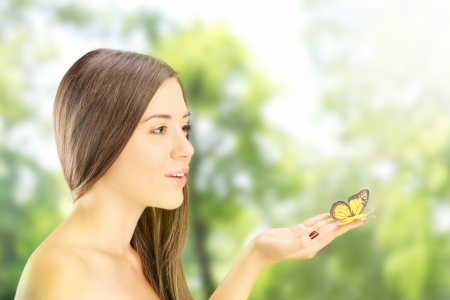 Beautiful young female holding a butterfly and posing outside in a park photo