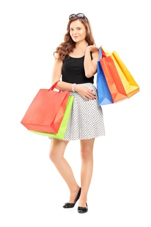 Full length portrait of an attractive young woman posing with shopping bags isolated on white background photo