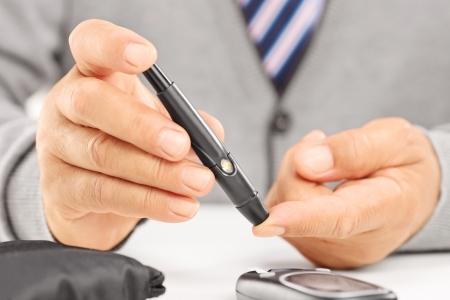 diabetes: Cerca de un paciente el nivel de az�car de medici�n diab�tica madura en la sangre con gluc�metro