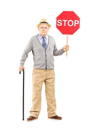 one senior adult man: Full length portrait of an angry mature gentleman holding a stop sign isolated on white background