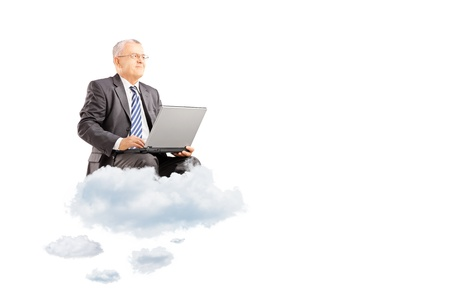 Mature businessman wearing suit and flying on clouds with laptop isolated on white background Stock Photo - 21588520