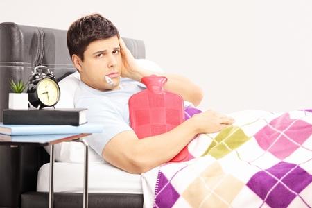 w�rmflasche: Kranker Mann im Bett mit Kopfschmerzen mit Thermometer in den Mund h�lt eine W�rmflasche