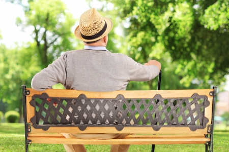 Mature man resting on a wooden bench in park photo