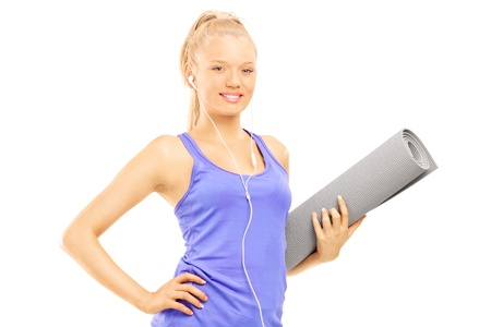 Young female holding an exercising mat isolated against white background