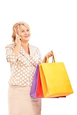 Blond mature woman holding shopping bags and talking on a phone isolated against white background photo