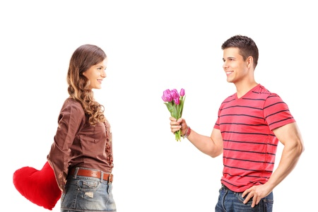 Smiling female holding red heart behind and man giving bouquet of flowers to her isolated on white background photo