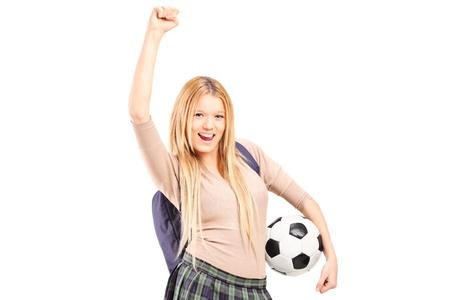 euphoric: Euphoric studentessa con zaino in possesso di un pallone da calcio isolato su sfondo bianco