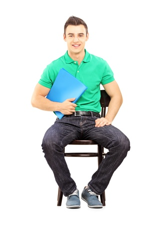 fascicule: Young handsome male sitting on a chair waiting for job interview isolated on white background Stock Photo