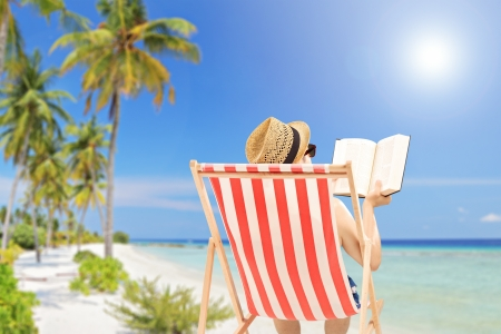 Young man lying on an outdoor chair and reading book, on a tropical beach Imagens