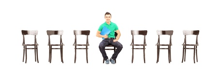 fascicule: Young handsome male sitting on a chair and waiting for job interview isolated on white background Stock Photo