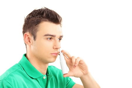 nasal drops: Young man spraying nose drops isolated on white background