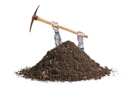 男性の肉体労働者が白い背景で隔離の穴を掘る