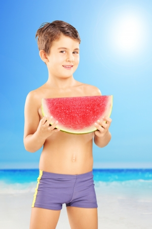 ni�o sin camisa: Chico sin camisa sosteniendo una rodaja de sand�a en una playa junto al mar Foto de archivo