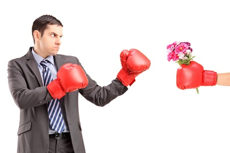 Angry man with boxing gloves hitting a hand with boxing glove and bunch of flowers isolated against white background photo