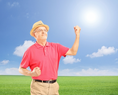 Happy senior man with raised hands gesturing happiness on a field, shot with a tilt and shift lens Stock Photo - 21893693