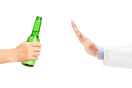 refusing: Medical doctor refusing a bottle of beer isolated on white background