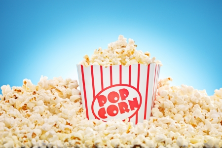 popped: Popcorn in classic box overflowing with freshly popped corn against a blue background Stock Photo