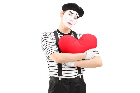 heartbreaking: Sad mime artist holding a red heart isolated on white background Stock Photo