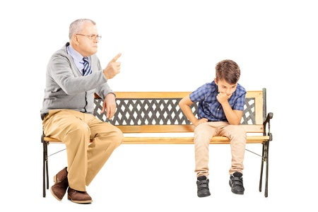 Angry grandfather shouting at his sad nephew, seated on a wooden bench, isolated on white background photo