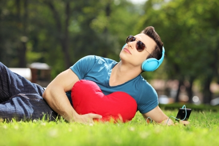 Handsome male lying on a green grass with red heart listening music photo