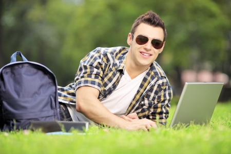 laptop outside: Smiling male student lying on a green grass and working on a laptop in park